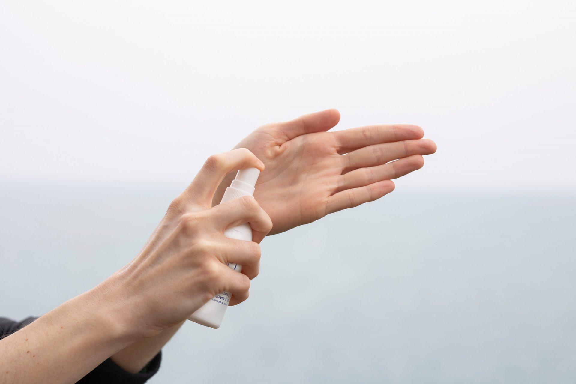 Kobieta aplikuje produkt biobójczy na dłonie