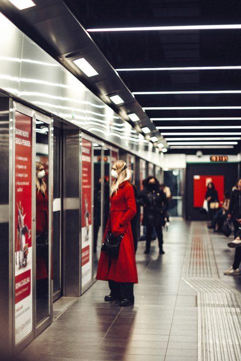 Kobieta stoi przed drzwiami do wagonu metra